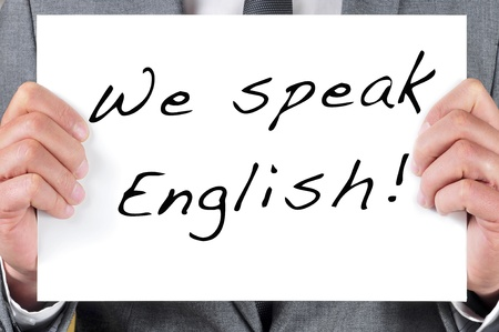 a man wearing a suit holding a signboard with the sentence we speak english written in it Stock Photo - 20330357