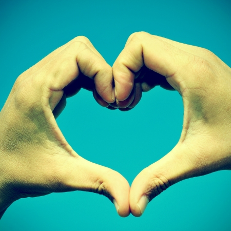 instagram: picture of man hands forming a heart over the blue sky, with a retro effect
