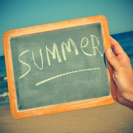 picture of someone on the beach holding a blackboard with the word summer written on it, with a retro effect photo