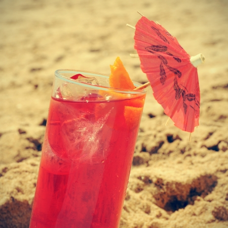picture of a refreshing red cocktail with a red umbrella on the sand of a beach, with a retro effect photo