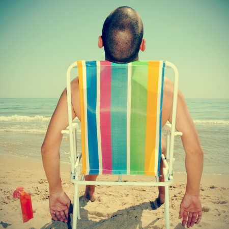picture of a man sunbathing on a deckchair on the beach with a cocktail, with a retro effect photo