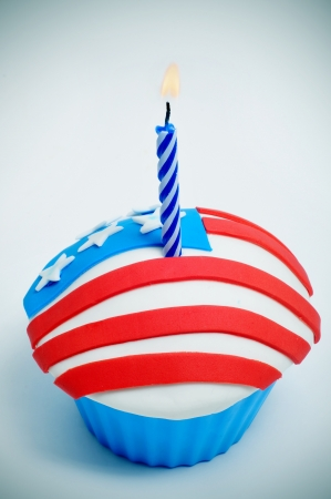 a cupcake, decorated with the colors and stars of the flag of the United States, with a lit candle photo