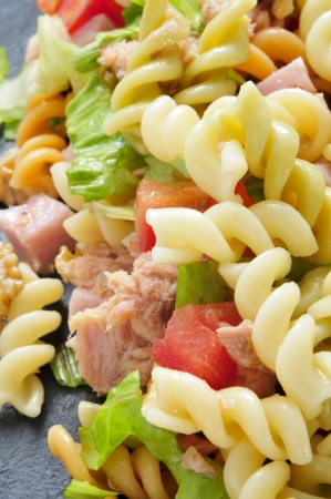 vertical bars: closeup of a refreshing pasta salad on a slate background