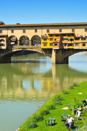 Florence, Italy - April 15, 2013: Ponte Vecchio and Arno River in Florence, Italy. This medieval bridge is one of the most visited landmarks in Florence and the most picturesque