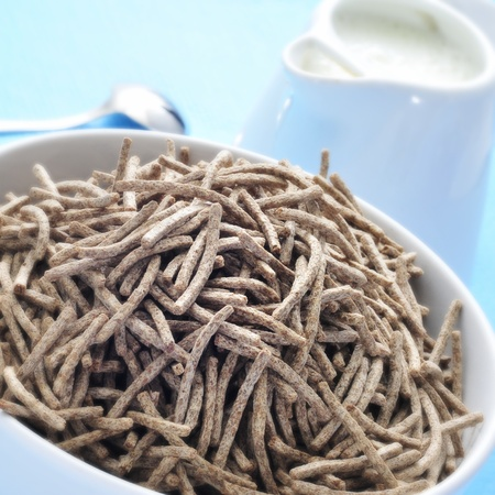 closeup of a bowl with cereal bran sticks and a milk pot on a blue surface photo