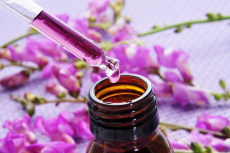 close-up van een druppelflesje en een stapel van paarse bloemen op een paarse achtergrond