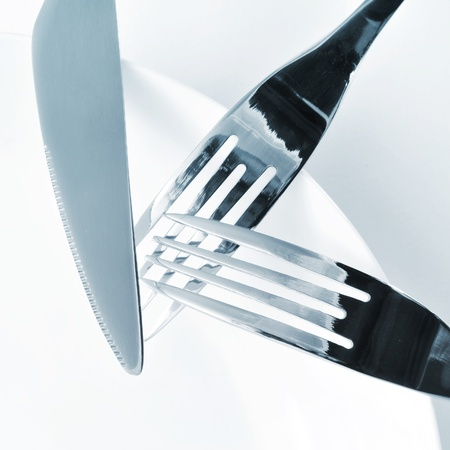 mealtime: closeup of a plate, knife and forks on a set table with a white tablecloth