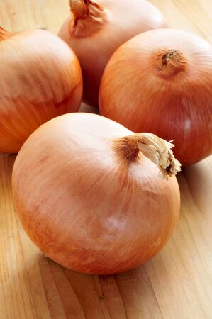 onion peel: some brown onions on a wooden table Stock Photo
