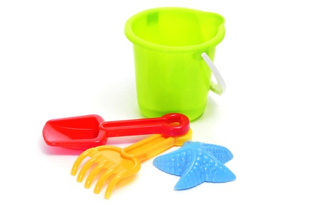 sand mold: closeup of a sand  beach toy set with a pail, shovel, rake and star-shaped mold of different colors on a white background