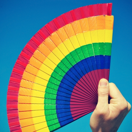 someone holding a hand fan painted with the colors of the gay pride flag over the blue sky, with a retro effect