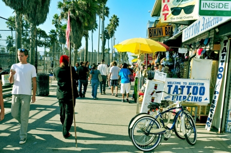 Venice, US - October 17, 2011: People walking in Ocean Front Walk, in Venice Beach, Venice, US. This boardwalk, 2.5 kilometer long, is full of colorful shops and food stalls