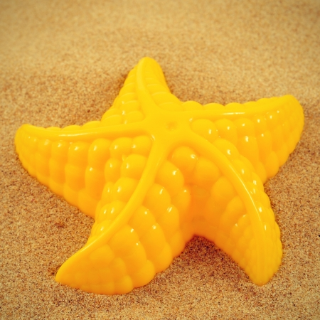 sand mold: closeup of a yellow starfish-shaped mold on the sand, with a retro effect