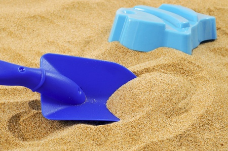 sand mold: closeup of a blue toy shovel and a blue fish-shaped mold on the sand Stock Photo