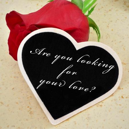 soltería: una rosa roja y una pizarra en forma de corazón con la frase ¿buscas el amor escrito en él, con un efecto retro
