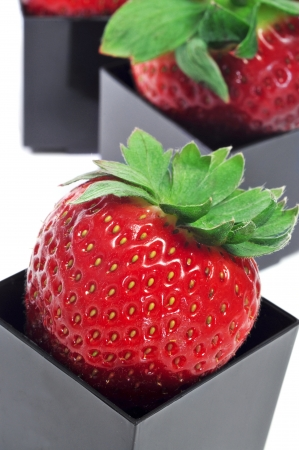 cubical: strawberries served in cubical bowls on a white background