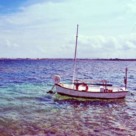 moorings: picture of a fishing boat in Estany des Peix lagoon, in Formentera, Balearic Islands, Spain, with a retro effect