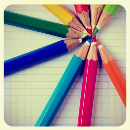 some pencil crayons of different colors on a notebook, with a frame and a retro effect photo