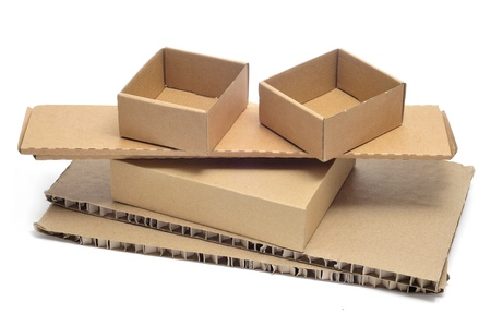 some brown cardboard boxes of different sizes and some pieces of corrugated cardboard on a white background photo