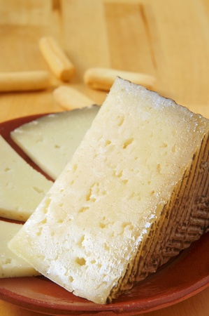 sliced cheese: closeup of a piece and some slices of manchego cheese from a Spain, and some bread sticks in the background