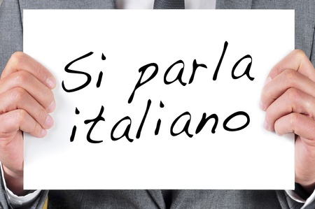 american banker: a man wearing a suit holding a signboard with the sentence si parla italiano, we speak italian, written in italian, in it Stock Photo