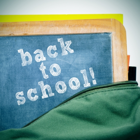 bookbag: sentence back to school written in a blackboard with a wooden frame, in a schoolbag, with a retro effect Stock Photo