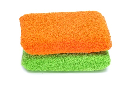 toweling: bath sponges of different colors on a white background