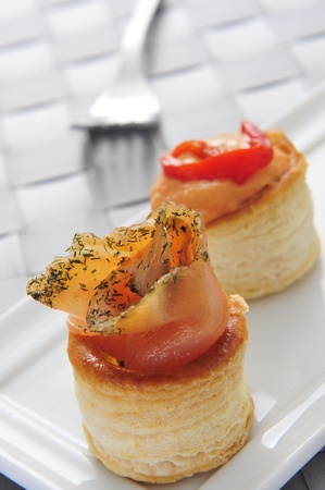 amuse: a plate with some different volauvents, one filled with smoked salmon and the other one filled with red pepper and cheese sauce, served as appetizer Stock Photo