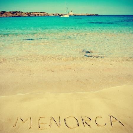 word Menorca written in the sand in Cala den Tortuga beach in Menorca, Balearic Islands, Spain, with a retro effect photo