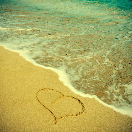 picture of a heart carved on the sand of a beach, with a retro effect photo