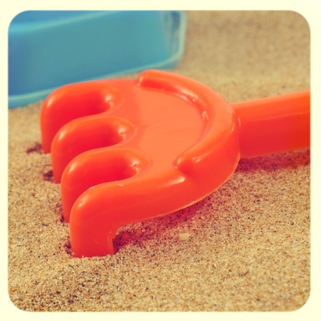 closeup of an orange rake on the sand of a beach or of a sandpit, with a retro effect photo