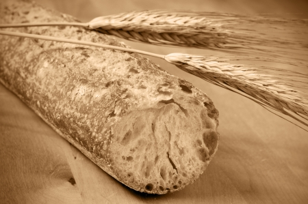 baguet: closeup of a ciabata bread and some wheat ears on a wooden surface