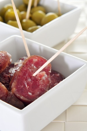 longaniza: slices of fuet, spanish cured sausage typical of Catalonia, and olives served as tapas Stock Photo