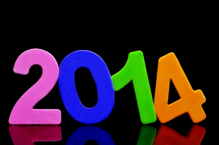 two thousand and fourteen: 2014, as the new year, written with numbers of different colors on a black background Stock Photo