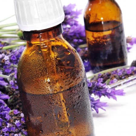 closeup of some dropper bottles with natural remedies and a pile of lavender flowers on a white background photo