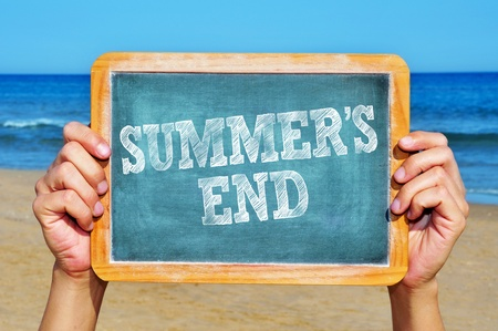retour: iemand met een bord met de zin zomers eind geschreven in het op het strand