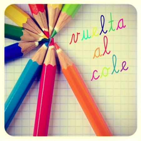 school year: vuelta al cole, back to school written in spanish, and some pencil crayons of different colors on a notebook, with a frame and a retro effect