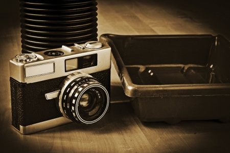 photographic effects: picture of a vintage reflex camera, a developing tank and a developing tray, with a retro effect