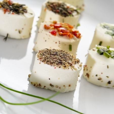 une plaque avec des différents canapés de fromage garni de différentes épices Banque d'images