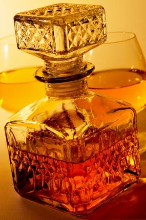 closeup of a vintage glass liquor bottle and some cognac glasses with liquor photo