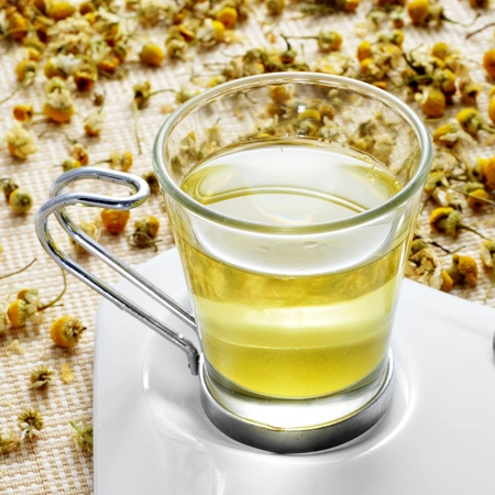 closeup of a glass cup with chamomile tea and a pile of dried chamomile flowers Stock Photo - 21374748