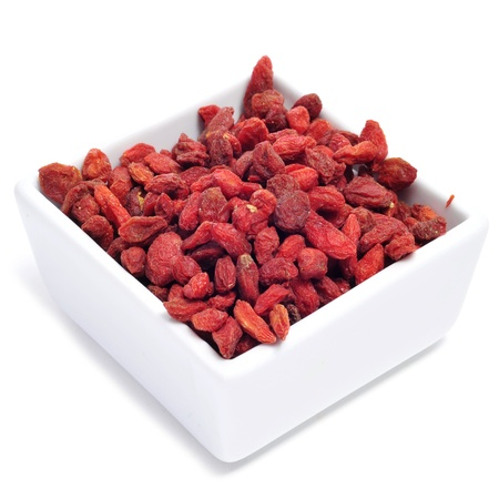 a bowl with dried goji berries on a white background photo