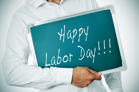 end of the day: a man holding a chalkboard with the sentence happy labor day written in it