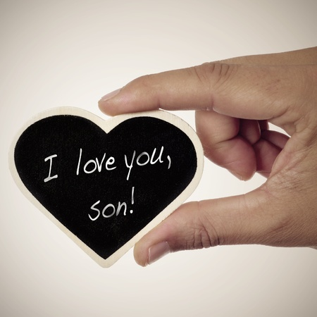 parental love: a man holding a heart-shaped blackboard with the sentence I love you, son written in it Stock Photo