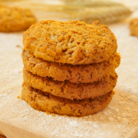 flak: closeup of some bran flake cookies on a wooden worktop peppered with flour and some wheat ears in the background