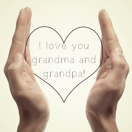 someone holding a drawn heart in his hands and the sentence I love you grandma and grandpa written in it photo
