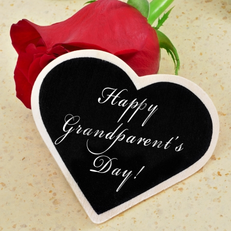 sentence happy grandparents day written with chalk on a heart-shaped blackboard with a red rose in the background Stock Photo