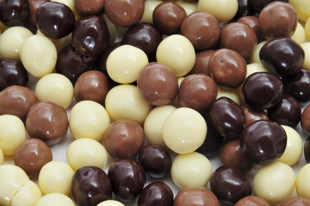 praline: closeup of some different ball-shaped chocolates made with black chocolate, white chocolate and milk chocolate
