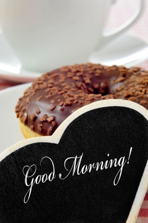 closeup of a heart-shaped blackboard with the sentence good morning written in it and a chocolate coated donut and a cup of coffee or tea in the background photo