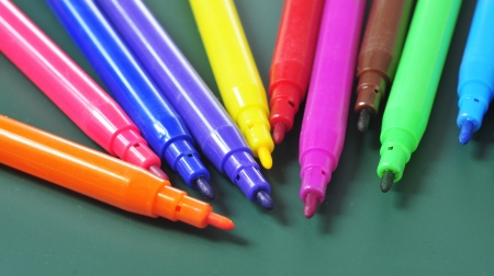 primary colors: a pile of felt-tip pens of different colors on a green chalkboard