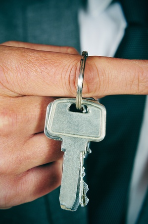 real estate agency: a man wearing a suit with a key ring in his hand Stock Photo